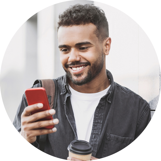 man smiling and using his cell phone